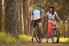 Um homem e uma mulher vá dar um ciclo nas madeiras Bicicleta à natureza fotografia de stock royalty free