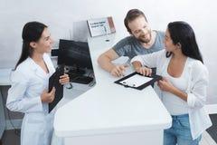 Um homem e uma mulher vieram ver um dentista They preencher os papéis necessários na sala de espera Imagem de Stock