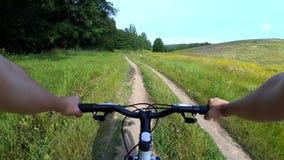 Um homem em um bicicleta-passeio está montando em uma estrada de terra filme