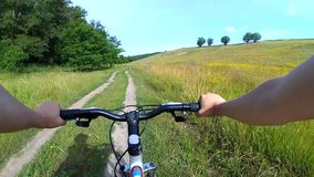 Um homem em um bicicleta-passeio está montando em uma estrada de terra video estoque