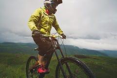 Um homem em um capacete da montanha que monta um Mountain bike monta em torno da natureza bonita no tempo nebuloso downhill foto de stock