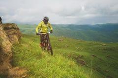Um homem em um capacete da montanha que monta um Mountain bike monta em torno da natureza bonita no tempo nebuloso downhill fotografia de stock