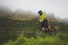Um homem em um capacete da montanha que monta um Mountain bike monta em torno da natureza bonita no tempo nebuloso downhill imagens de stock