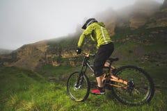 Um homem em um capacete da montanha que monta um Mountain bike monta em torno da natureza bonita no tempo nebuloso downhill imagens de stock royalty free