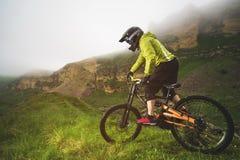 Um homem em um capacete da montanha que monta um Mountain bike monta em torno da natureza bonita no tempo nebuloso downhill imagem de stock