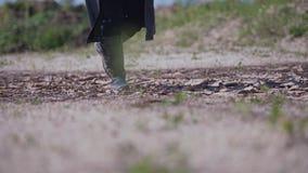 Um homem em um casaco preto e em umas botas de couro está na terra seca Tiro agradável filme
