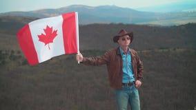 Um homem em um chapéu e óculos de sol, casaco de cabedal e calças de brim guardando uma bandeira canadense filme