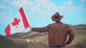 Um homem em um chapéu e óculos de sol, casaco de cabedal e calças de brim guardando uma bandeira canadense vídeos de arquivo