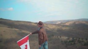 Um homem em um chapéu e óculos de sol, casaco de cabedal e calças de brim guardando uma bandeira canadense video estoque