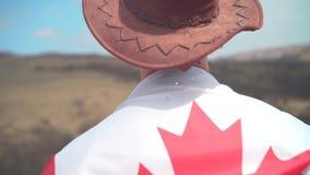 Um homem em um chapéu e óculos de sol, um casaco de cabedal e calças de brim jogou uma bandeira canadense no seu para trás video estoque