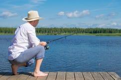 Um homem em um chapéu, sentando-se no cais, guardando uma vara de pesca e pescando, contra o céu azul e o lago fotos de stock royalty free