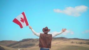Um homem em um chapéu, uma veste e um casaco de cabedal e umas calças de brim guarda uma bandeira canadense Um homem está com  filme