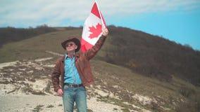 Um homem em um chap?u e ?culos de sol, casaco de cabedal e cal?as de brim guardando uma bandeira canadense video estoque