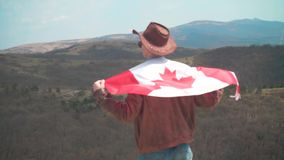 Um homem em um chap?u e ?culos de sol, um casaco de cabedal e cal?as de brim jogou uma bandeira canadense no seu para tr filme