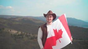 Um homem em um chap?u, uma veste e um casaco de cabedal e umas cal?as de brim est? guardando uma bandeira canadense A bandeira de video estoque