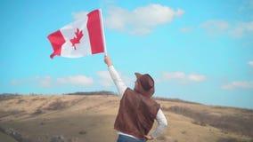 Um homem em um chap?u, uma veste e um casaco de cabedal e umas cal?as de brim guarda uma bandeira canadense Um homem est? com o s filme