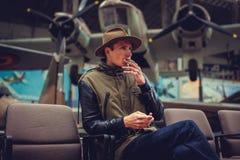 Um homem em um cigarro de fumo do chapéu na exposição dos aviões Imagem de Stock Royalty Free
