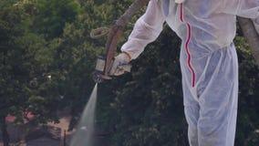 Um homem em um formulário especial no telhado usa uma solução química, pintando o telhado, isola o telhado filme