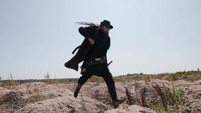 Um homem em passeios de um casaco preto e do chapéu em montes pequenos no deserto É com pressa em algum lugar vídeos de arquivo