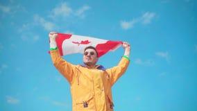 Um homem em um revestimento amarelo, na calças de ganga e nos vidros está nas montanhas e guarda a bandeira canadense com ambas filme