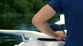 Um homem em um t-shirt azul que enfileira rapidamente em um barco no dia de verão branco da pá do rio vídeos de arquivo