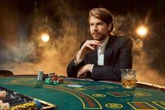 Um homem em um terno de negócio que senta-se na tabela de jogo Jogador masculino Paixão, cartões, microplaquetas, álcool, dado, j fotografia de stock