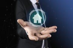 A um homem em um terno e em um laço aparece em suas mãos um gráfico futurista da casa Conceito de: domótica, aplicações home, imagens de stock royalty free