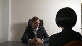 Um homem em um terno faz perguntas a uma mulher moreno em uma entrevista entrevista recruitment fotografia de stock