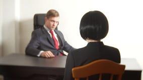 Um homem em um terno faz perguntas a uma mulher moreno em uma entrevista entrevista recruitment imagens de stock