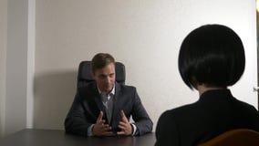 Um homem em um terno faz perguntas a uma mulher moreno em uma entrevista entrevista recruitment foto de stock royalty free