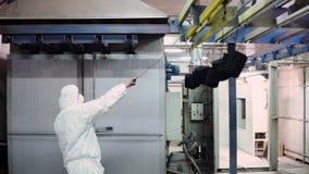 Um homem em um terno protetor abre as portas ao forno e traz lá os detalhes video estoque