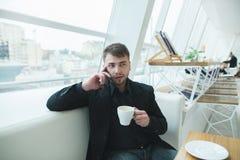 Um homem em um terno que senta-se em uma tabela em um café brilhante perto da janela e que fala no telefone Imagem de Stock