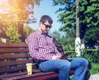 Um homem em um banco em um parque da cidade, leu uma mensagem na tabuleta, olhando um filme ou um programa televisivo, ao lado de Foto de Stock