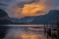 Um homem em um barco no lago no por do sol em Áustria Imagens de Stock