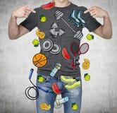 Um homem em um bom formulário físico está indicando os dedos nos ícones coloridos do esporte Fundo concreto um conceito de uma sa Imagem de Stock