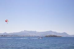 Um homem em um paraglider alaranjado está voando após um barco que navegue Fotografia de Stock