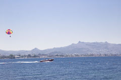 Um homem em um paraplane está voando após um barco esse velas pelo mar a Fotografia de Stock