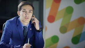 Um homem em um terno de negócio está falando no telefone relutantemente filme