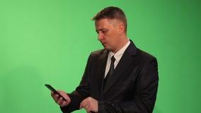 Um homem em um terno de negócio lança com a notícia em seu smartphone video estoque