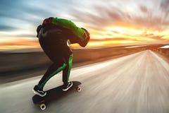 Um homem em um terno do capacete e do couro, em uma cremalheira na alta velocidade, monta em um longboard longo para para baixo s Imagem de Stock Royalty Free
