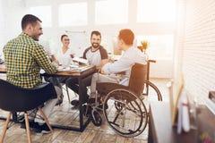 Um homem em uma cadeira de rodas comunica-se alegremente com os empregados do escritório durante uma reunião de negócios Fotografia de Stock Royalty Free