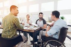 Um homem em uma cadeira de rodas comunica-se alegremente com os empregados do escritório durante uma reunião de negócios Foto de Stock Royalty Free