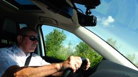 Um homem em uma camisa branca e em óculos de sol está conduzindo um carro filme