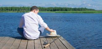 Um homem em uma camisa branca, sentando-se no cais, guardando um chapéu, encontrando-se ao lado de uma vara de pesca para pescar, fotografia de stock