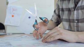 Um homem em uma camisa de manta, um par de tesouras corta o papel de traçado que mostra o plano filme
