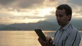 Um homem em uma camisa verifica mensagens na tabuleta durante o nascer do sol na praia do oceano Cores maravilhosas do céu vídeos de arquivo