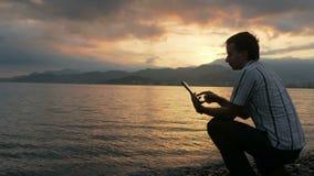 Um homem em uma camisa verifica mensagens na tabuleta durante o nascer do sol na praia do oceano Cores maravilhosas do céu video estoque