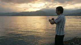 Um homem em uma camisa verifica mensagens no relógio esperto durante o nascer do sol na praia do oceano e das montanhas Há um arq video estoque