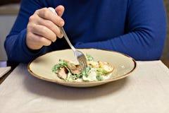 Um homem em uma camiseta azul com uma forquilha em sua mão que come uma salada Close-up fotografia de stock royalty free