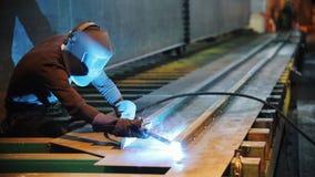 Um homem em uma construção do metal de soldas do terno protetor vídeos de arquivo